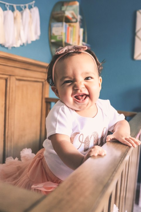 baby girl standing in crib with big smile and bow family at home baby photography aribella photography