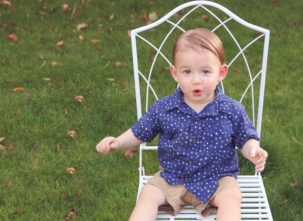 boy toddler in blue button down shirt sitting in white chair toddler baby family photography aribella photography