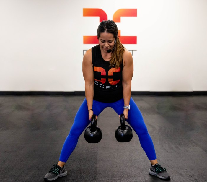 brunette woman with bright blue leggings lifting kettle bells in a gym