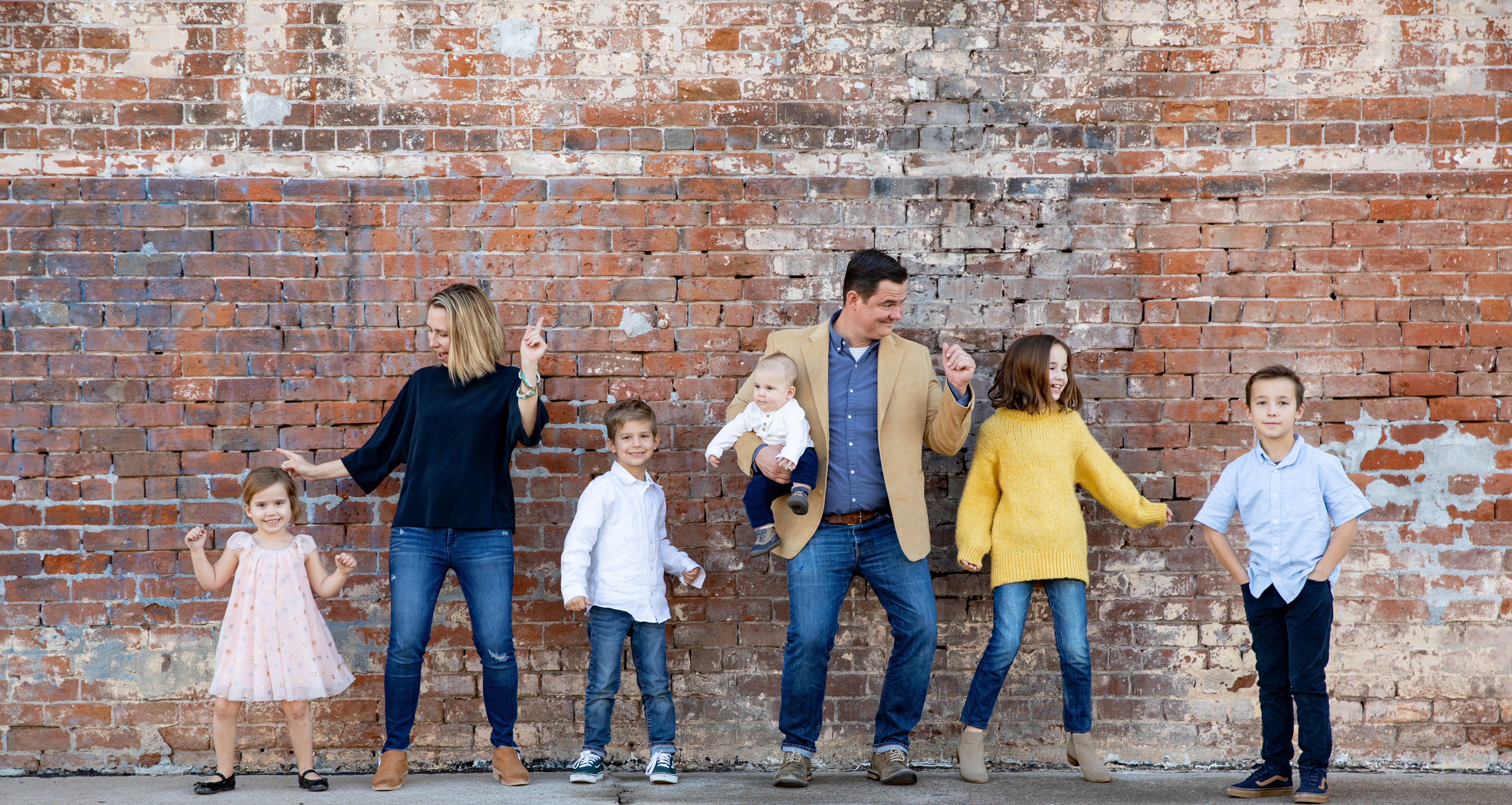 large family of five kids stands and dances with parents in front of brick wall kids children family picture aribella photography