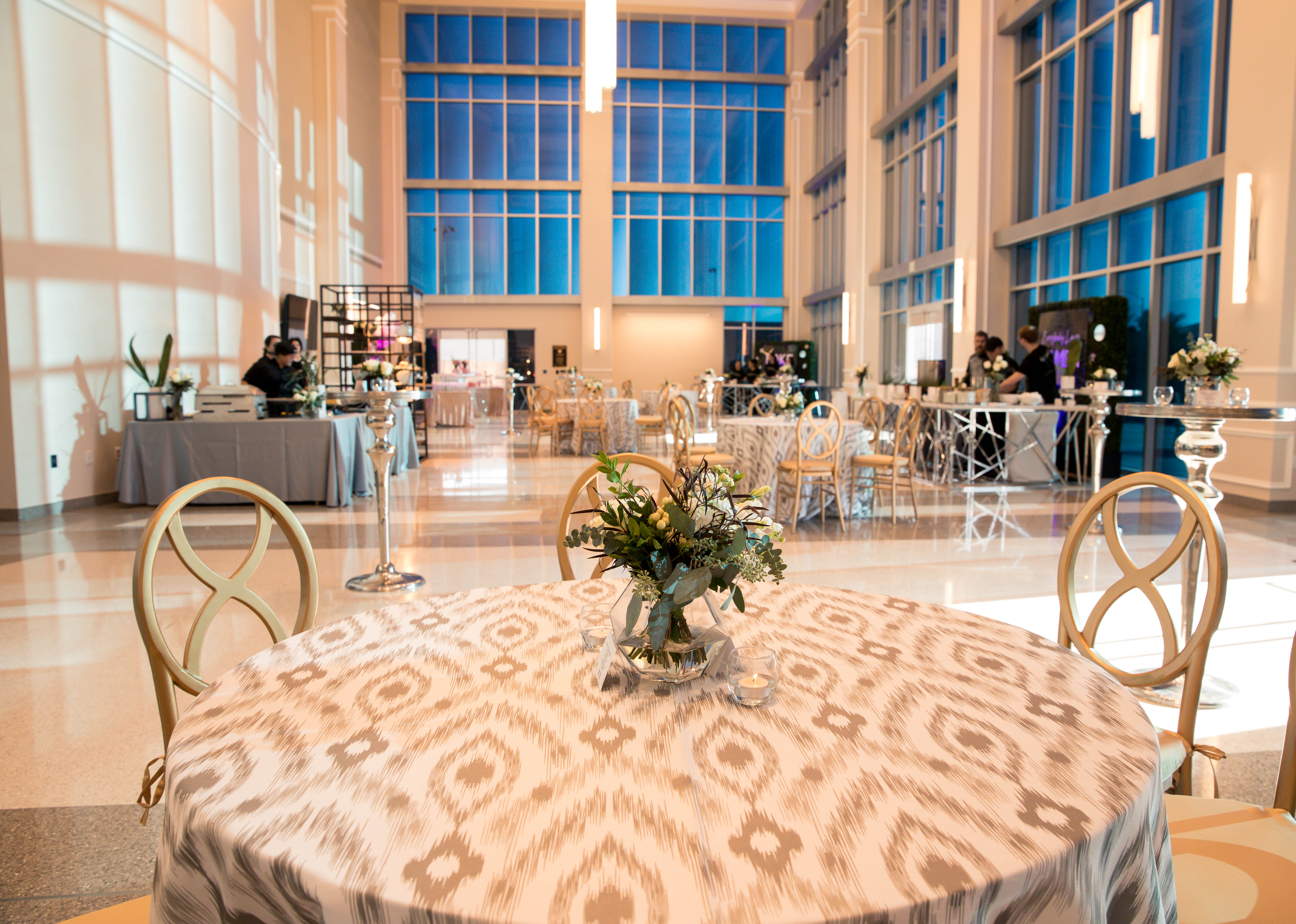 large white room with tall windows tan ikat pattern table cloth and ornate circle chairs aribella photography event pictures