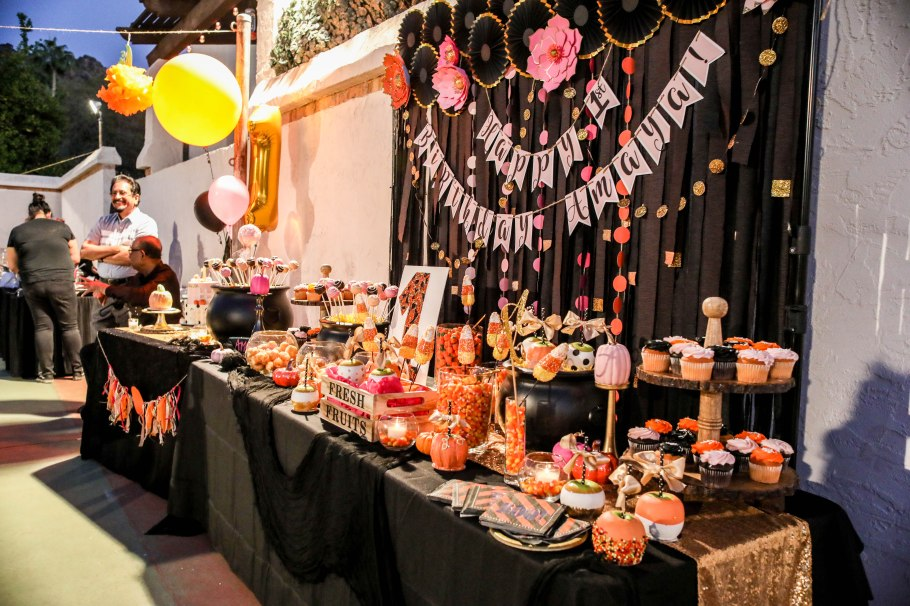 black curtain behind a black table filled with halloween themed birthday treats aribella photography eent pictures