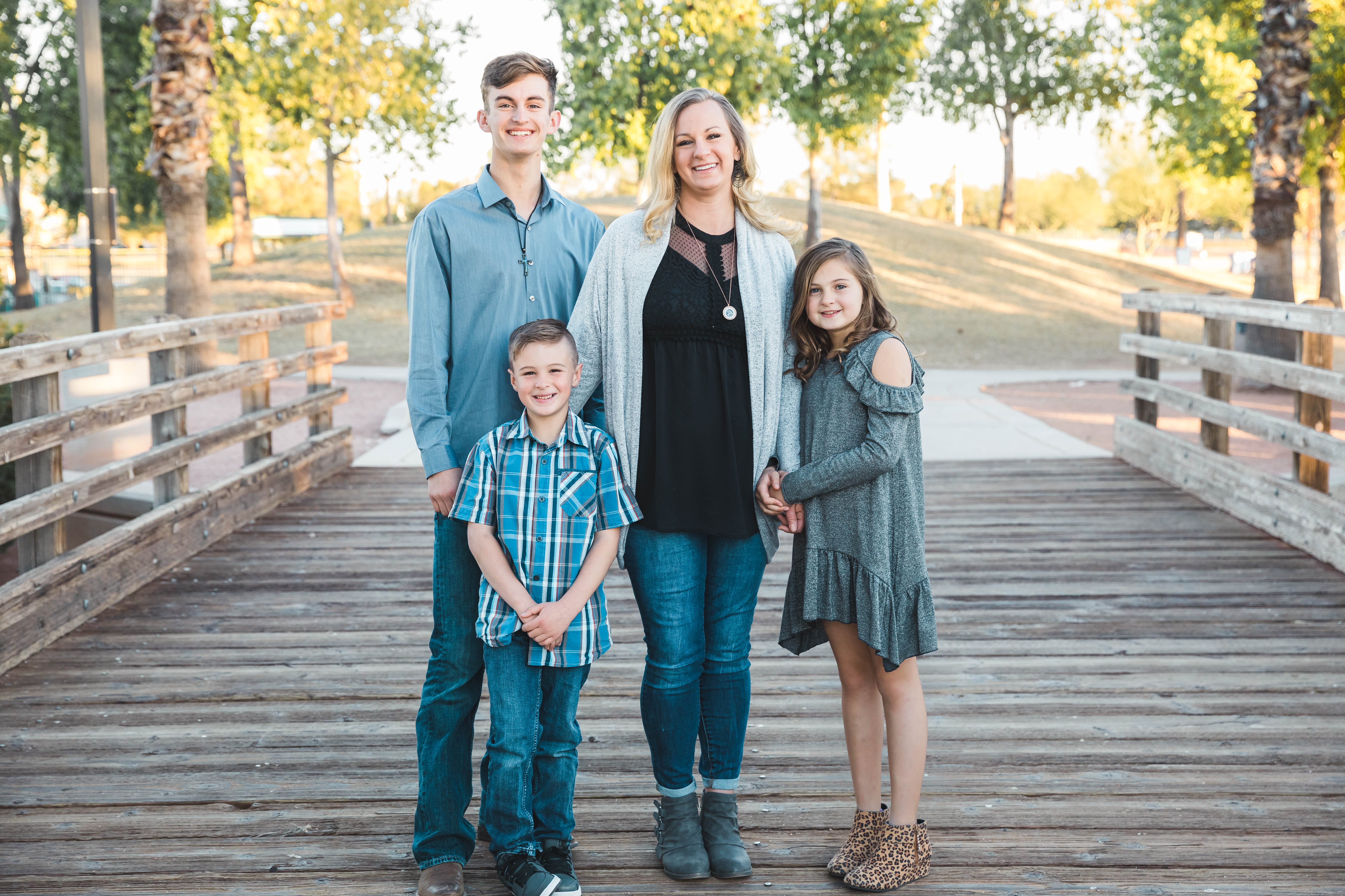 family of four stands on bridge mom teenage son middle school daughter young son aribella photography family kids children photography pictures photos
