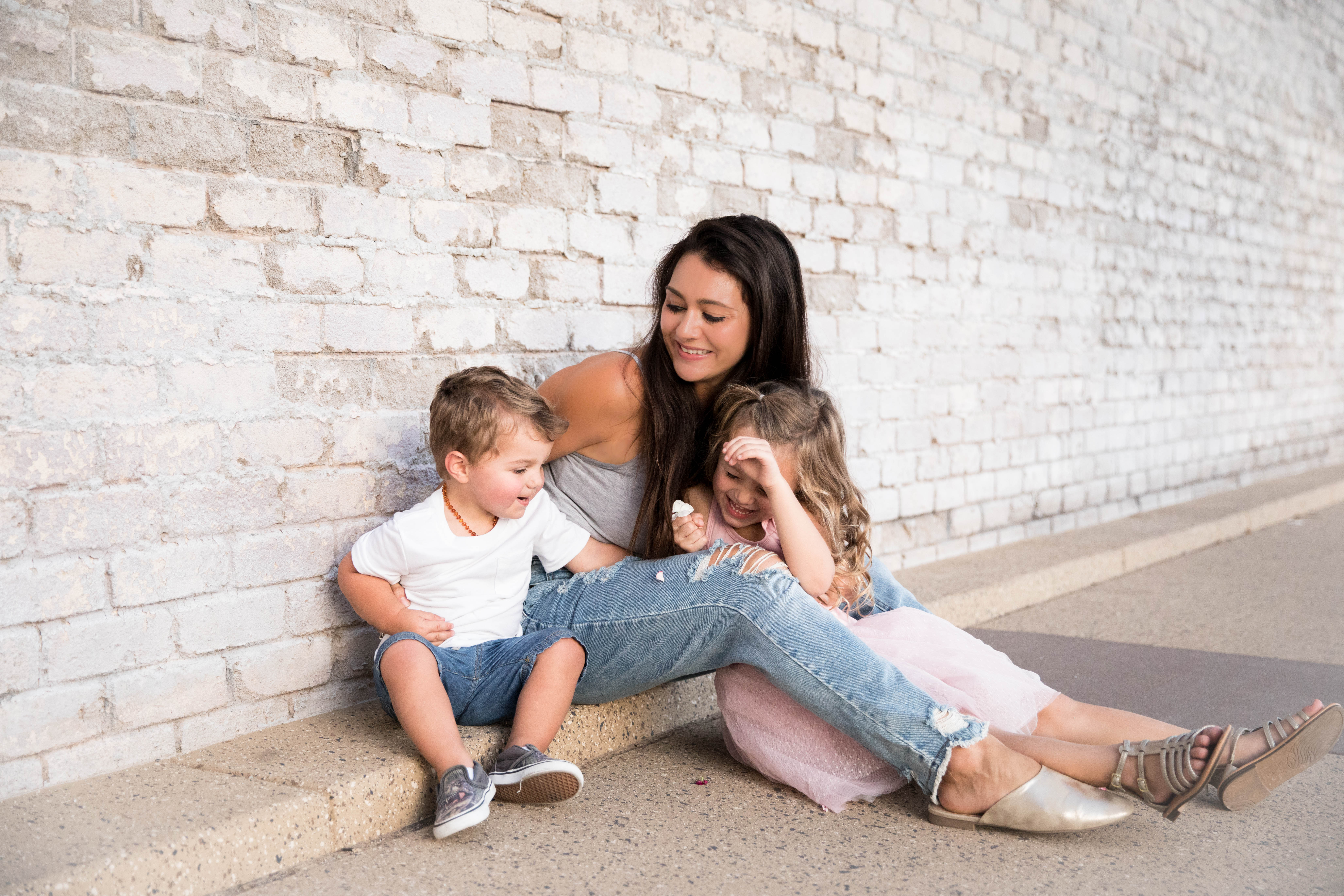 white brick wall with mom and two young children aribella photography kids children family photos pictures