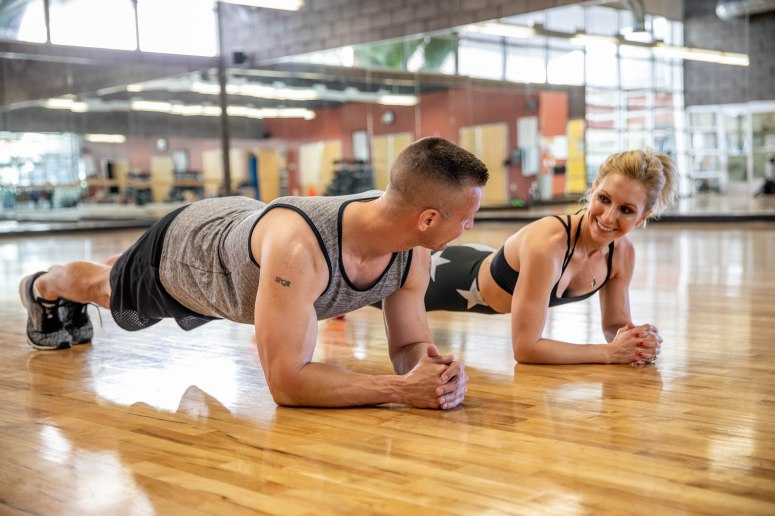 man and woman hold plank on a wooden gym floor aribella photography brand branding photography